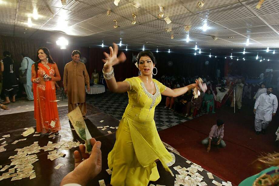 In this Sunday, Oct. 21, 2012, photo, a man, bottom left, offers money to Sonia, 26, a transgender Pakistani, while dancing at the birthday party of her transgender friend, Sana, not pictured, in Rawalpindi, Pakistan. Transgender people live in a tenuous position in conservative Pakistan, where the roles of the sexes are traditionally starkly drawn. Families often push them out of the home when they're young, forcing many to prostitute themselves to earn a living. One role where they are tolerated is as dancers at weddings and other celebrations at which men and women are strictly segregated.(AP Photo/Anjum Naveed) Photo: Anjum Naveed, Associated Press