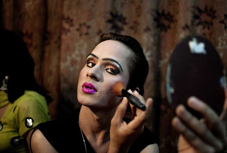 In this Thursday, Oct. 18, 2012, photo, Kate Heart, 19, a Pakistani transgender, applies makeup before heading to a wedding party where she will perform, in Rawalpindi, Pakistan. Transgender people live in a tenuous position in conservative Pakistan, where the roles of the sexes are traditionally starkly drawn. Families often push them out of the home when they're young, forcing many to prostitute themselves to earn a living. One role where they are tolerated is as dancers at weddings and other celebrations at which men and women are strictly segregated. (AP Photo/Anjum Naveed) Photo: Anjum Naveed, Associated Press