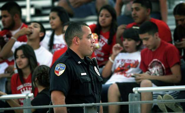 A Laredo Independent School District police officer scans the crowd at a recent Martin High School football game at Shirley Field.  Laredo players and coaches deal with issues related to the recent violence across the border. Thursday.  Oct. 4, 2012. Photo: BOB OWEN, San Antonio Express-News / © 2012 San Antonio Express-News