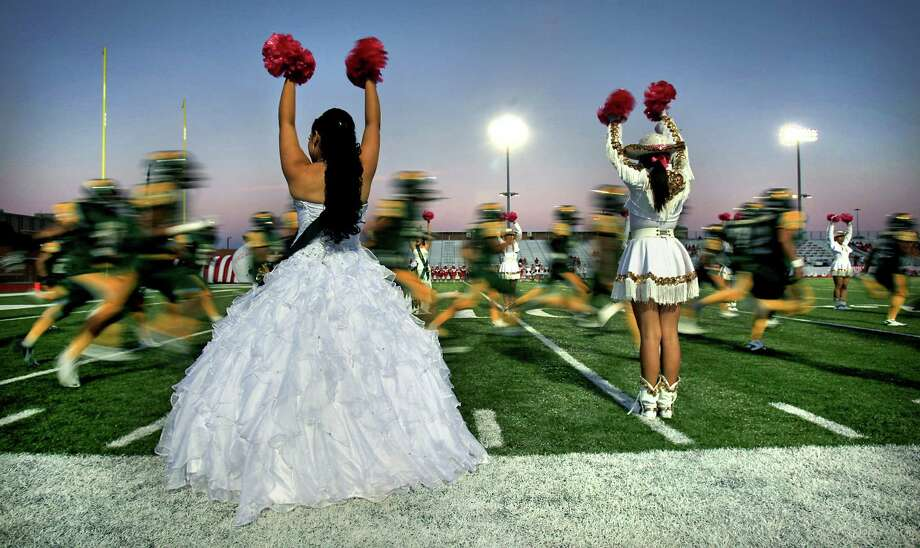 A Nixon High School Homecoming Queen candidate who is also a cheerleader at the Laredo school, cheers as the Nixon football team takes the field at the begining of their Friday night game Oct. 5, 2012, at LISD's Shirley Field. Photo: BOB OWEN, San Antonio Express-News / © 2012 San Antonio Express-News