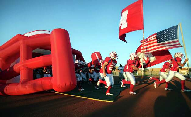Members of the Martin High School football team take the field for a game against Corpus Christi Flower Bluff at Shirley Field in Laredo.  Some sports teams in the state are affraid of traveling to Laredo for games, due to the recent violence across the border. Thursday.  Oct. 4, 2012. Photo: BOB OWEN, San Antonio Express-News / © 2012 San Antonio Express-News