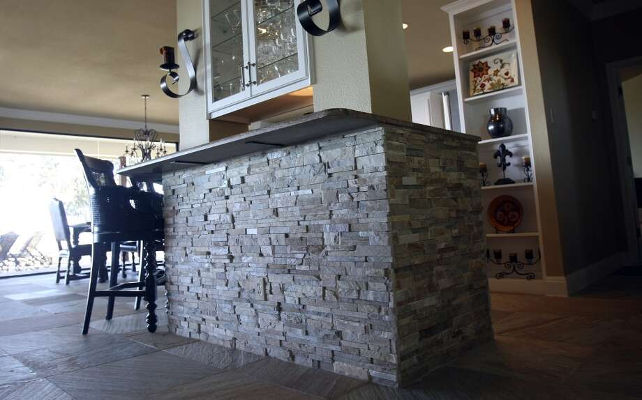 Jimmy Franklin added slate floors and the stack stone feature to the kitchen bar area. The  original kitchen cabinets were repainted and new hardware was added. (San Antonio Express-News)