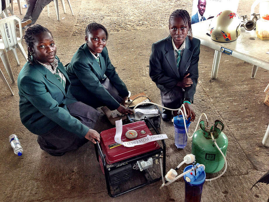 Duro-Aina Adebola, Akindele Abiola and Faleke Oluwatoyin, 14, and Bello Eniola, 15, pose with their urine-powered generator. Photo: Maker Faire Africa