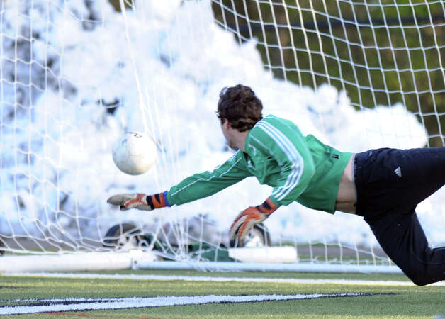 New Canaan goalkeep Michael Powell tries to stop a goal during Friday's soccer game at New Canaan High School on November 9, 2012. Photo: Lindsay Niegelberg / Stamford Advocate