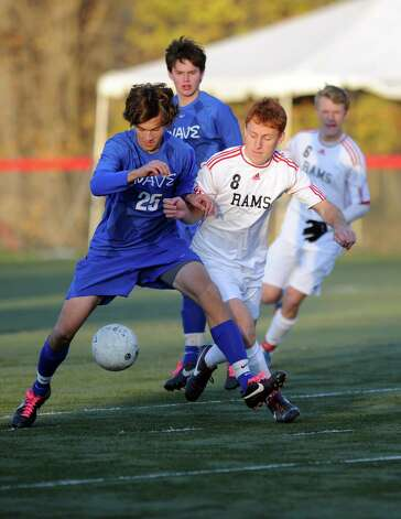 Darien's Alexei Gunya, left, and New Canaan's Eric Persky, right, compete for control of the ball during Friday's soccer game at New Canaan High School on November 9, 2012. Photo: Lindsay Niegelberg / Stamford Advocate