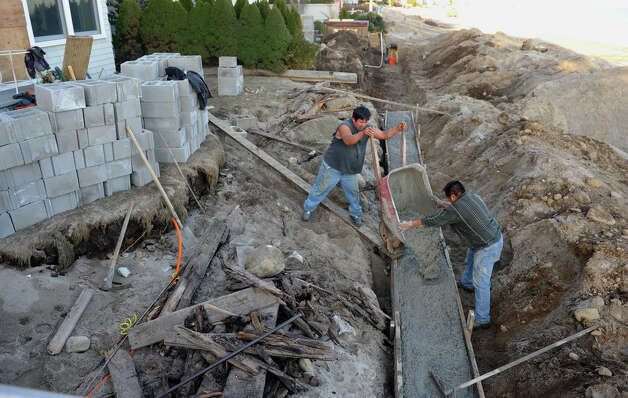 Workers rebuild a seawall that sustained damage from Hurricane Sandy along Fairfield Beach Road in Fairfield, Conn. on Friday November 9, 2012. Photo: Christian Abraham / Connecticut Post