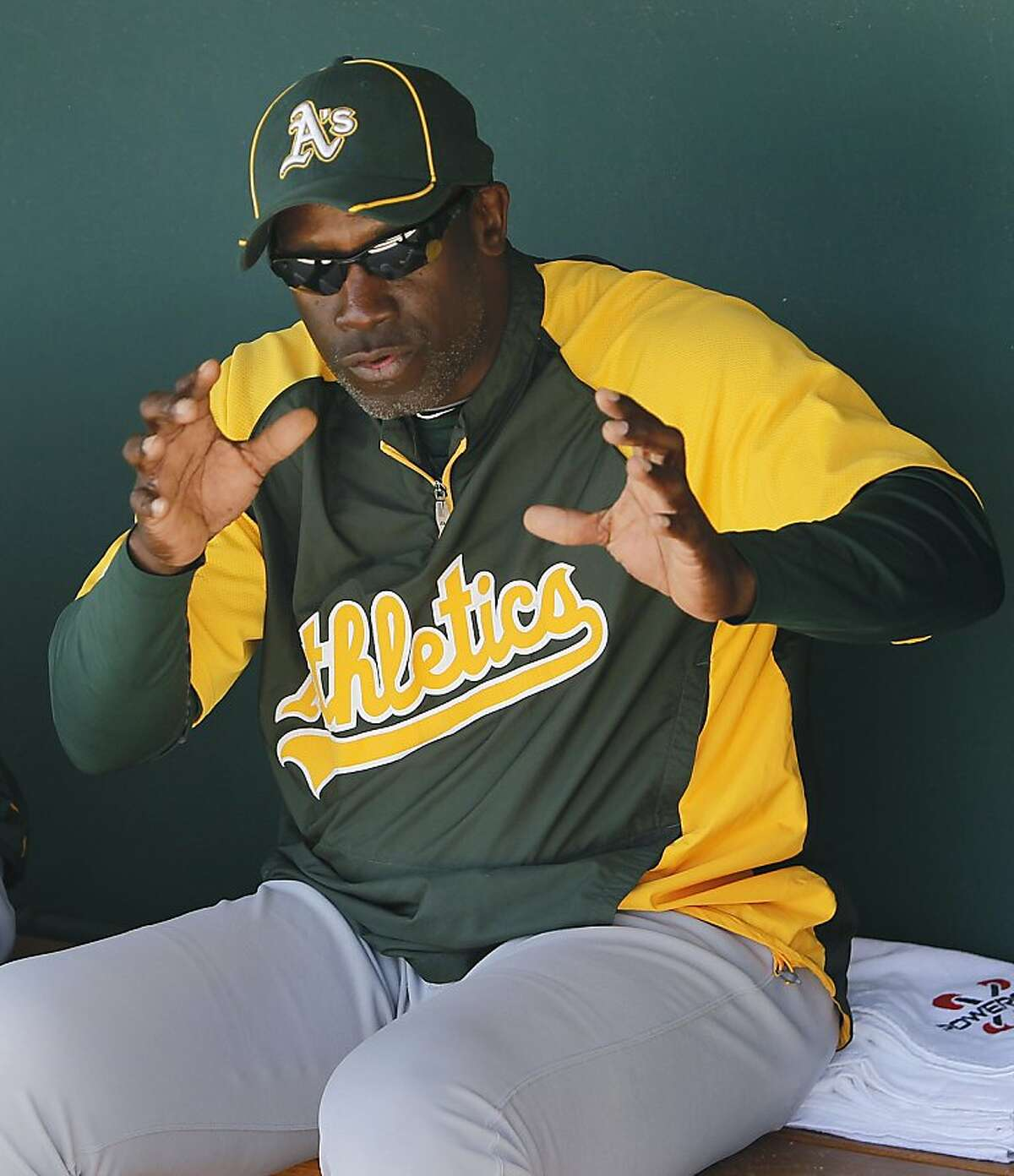 Batting coach Chili Davis works with a player in the dugout before the Oakland A's Cactus League spring training game against the Los Angeles Dodgers in Glendale, Ariz. on Thursday, March 8, 2012.