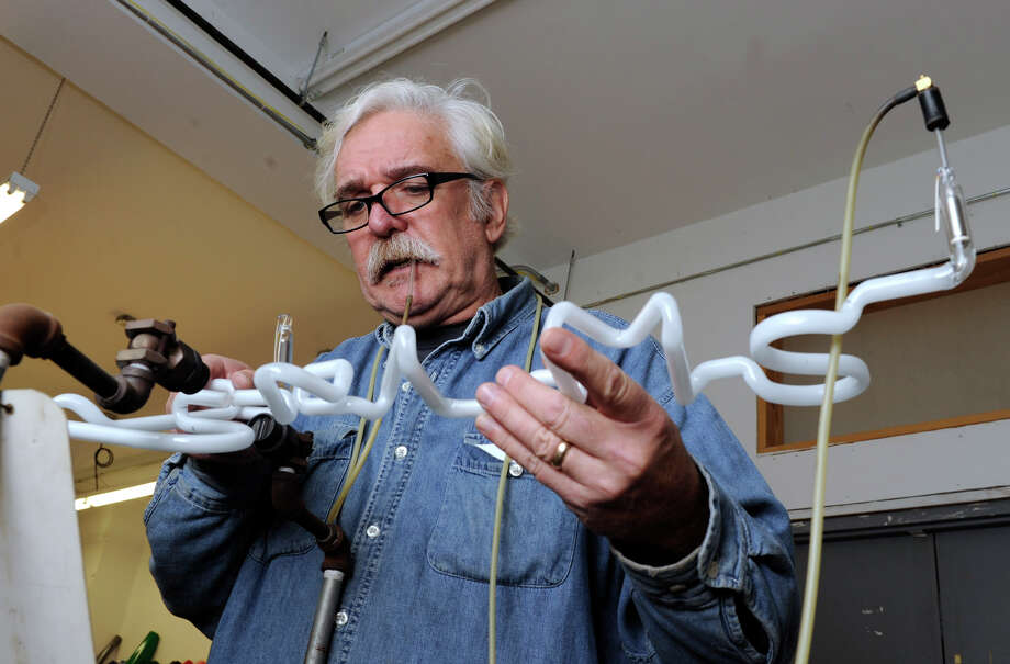 Howard Bujese, owner of The Sign Shop on Greenwood Avenue in Bethel, uses a torch to bend and mold a neon sign, Wednesday, Nov. 7, 2012. Photo: Carol Kaliff / The News-Times