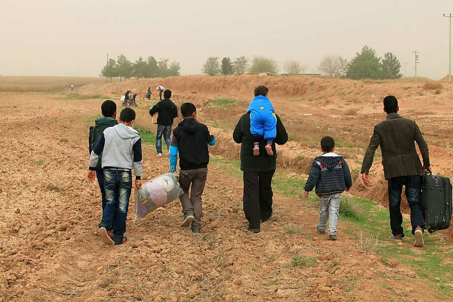 Syrians, among the thousands of people who crossed the border into Turkey, flee as clashes between troops and rebel forces intensify. Photo: -, AFP/Getty Images