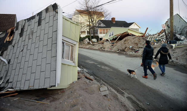 Kevin and Deanna Bull walk their dogs past homes which were destroyed during Hurricane Sandy along Fairfield Beach Road in Fairfield, Conn. on Friday November 9, 2012. Photo: Christian Abraham / Connecticut Post