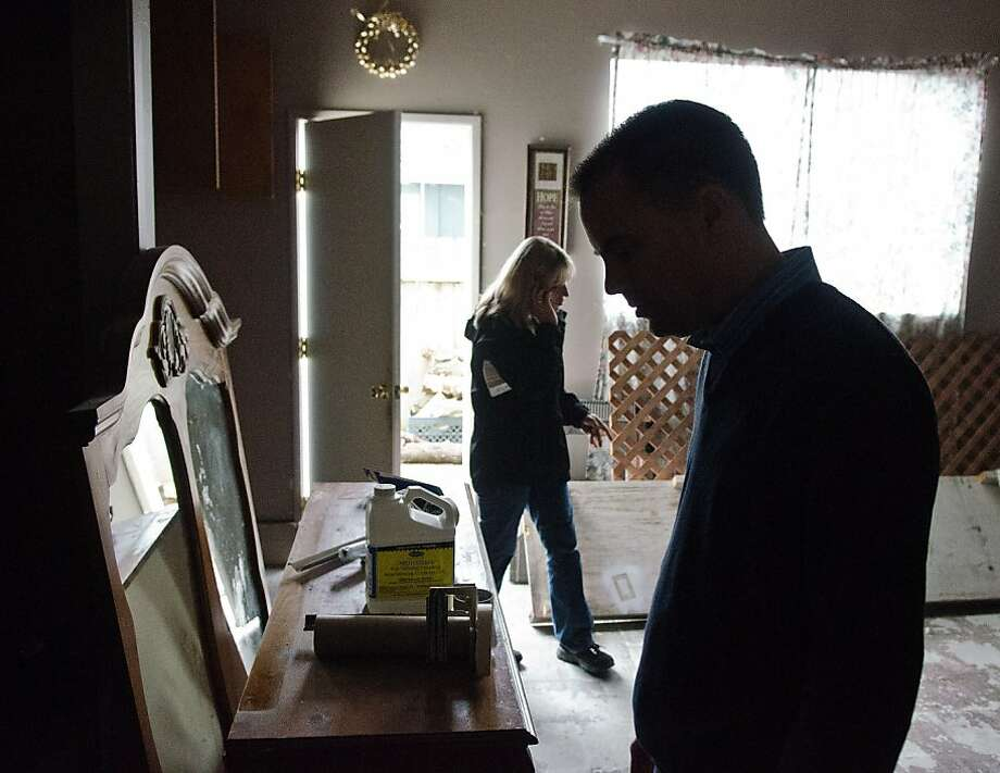 Praxis Captial managing partner Brian Burke, right, and project coordinator Marit Cole inspect the garage of a home Praxis Captial bought at a foreclosure auction for $182,000 in September and are currently rehabbing to rent out for about $1950 a month in Santa Rosa, California on November 8, 2012. Photo: Alvin Jornada, Special To The Chronicle