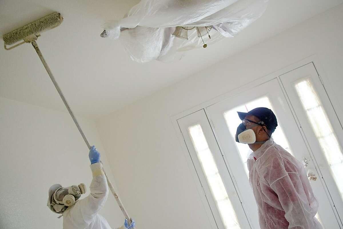 Jose Salgado, left, and his brother Osvaldo Salgado paint the interior of a home Praxis Captial bought at a foreclosure auction for $182,000 in September and are currently rehabbing to rent out for about $1950 a month in Santa Rosa, California on November 8, 2012.