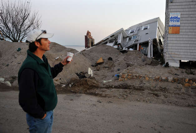 Resident Carl Walker looks at some of the destruction left behind in the aftermath of Hurricane Sandy along Fairfield Beach Road in Fairfield, Conn. on Friday November 9, 2012. Photo: Christian Abraham / Connecticut Post