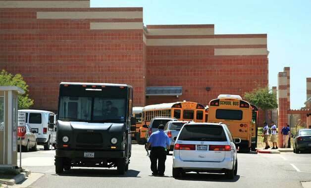 A security guard at Cigarroa High School in Laredo checks vehicles entering and leaving the school parking lot as football players board buses to go to a game in Alice, TX.  Friday.  Oct. 5, 2012. Photo: BOB OWEN, San Antonio Express-News / © 2012 San Antonio Express-News
