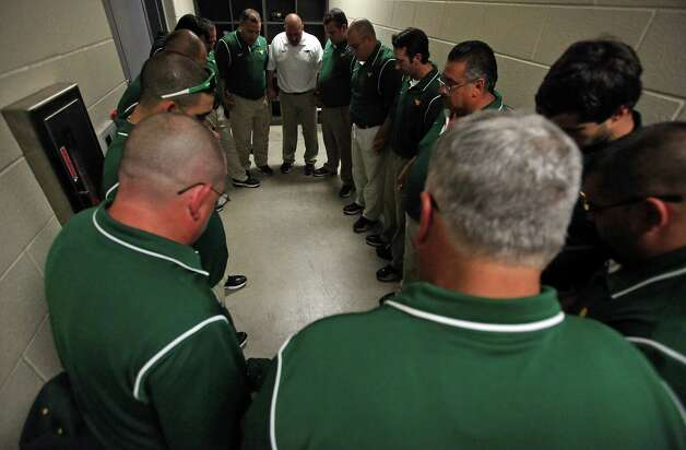 The football coaching staff of Nixon High School gathers for prayer lead by Head Coach Tommy Ramirez, in white shirt, before a game at Shirley Field in Laredo, Friday,  Oct. 5, 2012. Photo: BOB OWEN, San Antonio Express-News / © 2012 San Antonio Express-News