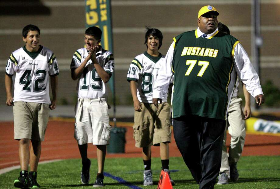 Laredo Independent School District Superintendent Dr. Marcus Nelson, right, wears his Nixon Mustangs shirt as he walks with Jonathan Rodriguez, left to right, Jorge Salazar, Ricardo Bernal, and Manuel Rodriguez (behind Nelson), all members of the Nixon freshman football team.  Nelson, in his third year as superintendent, is a graduate of Judson High School and played football wearing #77.  He has a jersey with his number, for every high school team in LISD.  Friday,  Oct. 5, 2012. Photo: BOB OWEN, San Antonio Express-News / © 2012 San Antonio Express-News