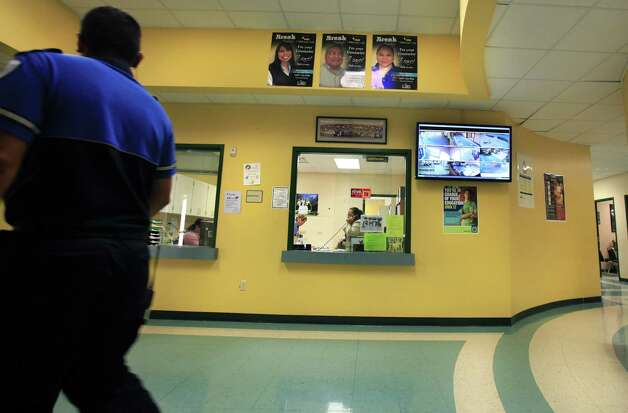 A police officer passes through the main lobby at Nixon High School in Laredo, where they have multiple screens from security cameras all over campus.  Thursday.  Oct. 4, 2012. Photo: BOB OWEN, San Antonio Express-News / © 2012 San Antonio Express-News