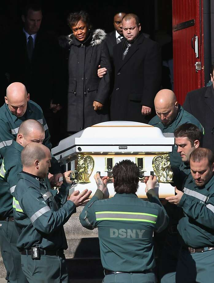 NEW YORK, NY - NOVEMBER 09:  Glenda Moore (C) watches as New York sanitation department workers carry a casket containing the bodies of her two sons after their funeral at the St. Rose of Lima Catholic church on November 9, 2012 in the Brooklyn borough of New York City. Brandon Moore, 2, and his brother Connor Moore, 4, were swept away from the arms of their mother Glenda as she fled with them from Superstorm Sandy floodwaters in New York's Staten Island borough to seek safety with family in Brooklyn the night of the storm. She is married to New York sanitation worker Damian Moore, and dozens of workers and officials from the sanitation department attended the funeral ceremony.  (Photo by John Moore/Getty Images) Photo: John Moore, Getty Images