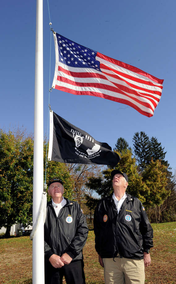 Brendan Sniffin, left, and Kenneth Post Jr., both of Danbury and Korean War veterans, are the ones who raise and lower the flag from full to half staff. Photo: Carol Kaliff / The News-Times