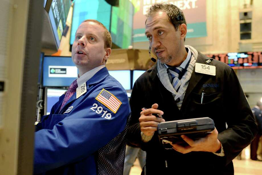 FILE -In this Thursday, Nov. 8, 2012, file photo, Robert Nelson II of Barclays, left, and Fady Tanios of Raven Securities work on the floor of the New York Stock Exchange, in New York. (AP Photo/Henny Ray Abrams) Photo: Henny Ray Abrams