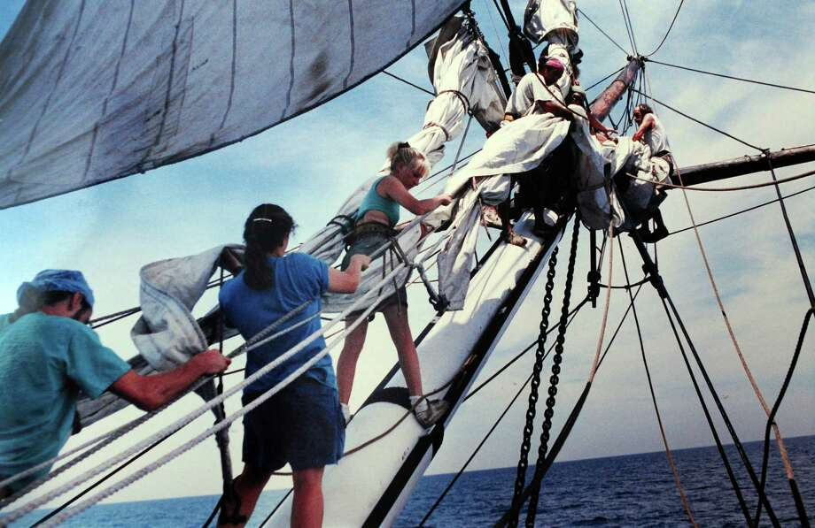 A photo of of Michael Freeman, aboard The Rose.  Freeman is pictured on the far right perched on the spritsail yard sending more sail aloft. Photo: Contributed Photo