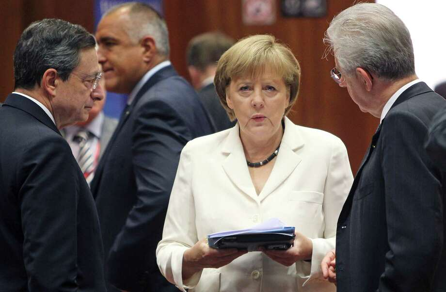 FILE - In this June 29, 2012 file photo, German Chancellor Angela Merkel, center, speaks with European Central Bank President Mario Draghi, left, and Italian Prime Minister Mario Monti during a round table meeting at a EU Summit in Brussels. The worst of Europe's financial crisis appears to be over. European leaders have taken steps to ease the panic that has plagued the region for three turbulent years. Much of the credit for easing Europe's financial crisis goes to the European Central Bank, which has become more aggressive over the past year under the leadership of Mario Draghi. Merkel has also helped ease financial tensions across the region by speaking more forcefully about the need to hold the euro together. (AP Photo/Michel Euler, File) Photo: Michel Euler