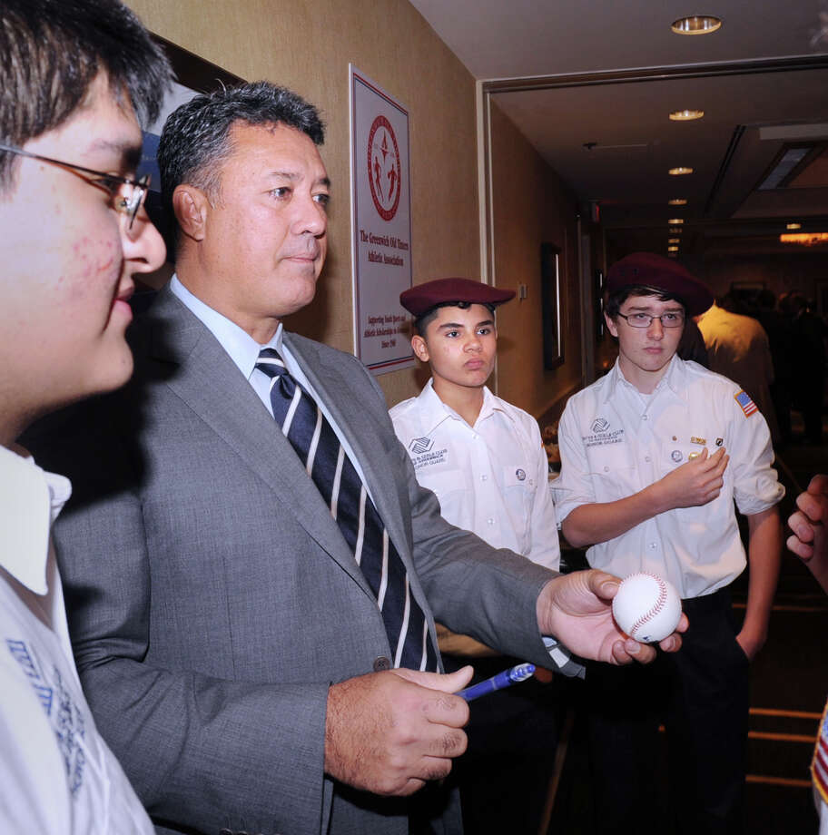 Former New York Mets pitching star Ron Darling, second from left, autographs a baseball during the 52nd Annual Greenwich Old Timers Awards Dinner at the Hyatt Regency Greenwich, Friday night, November 9, 2012. Standing from left to right, with Darling, are Greenwich Boys & Girls Club Honor Guard members, Victor Sanchez, 15, Emilio Rojas, 13, and Peter Hughes, 16. Darling was honored during the dinner. Photo: Bob Luckey / Greenwich Time