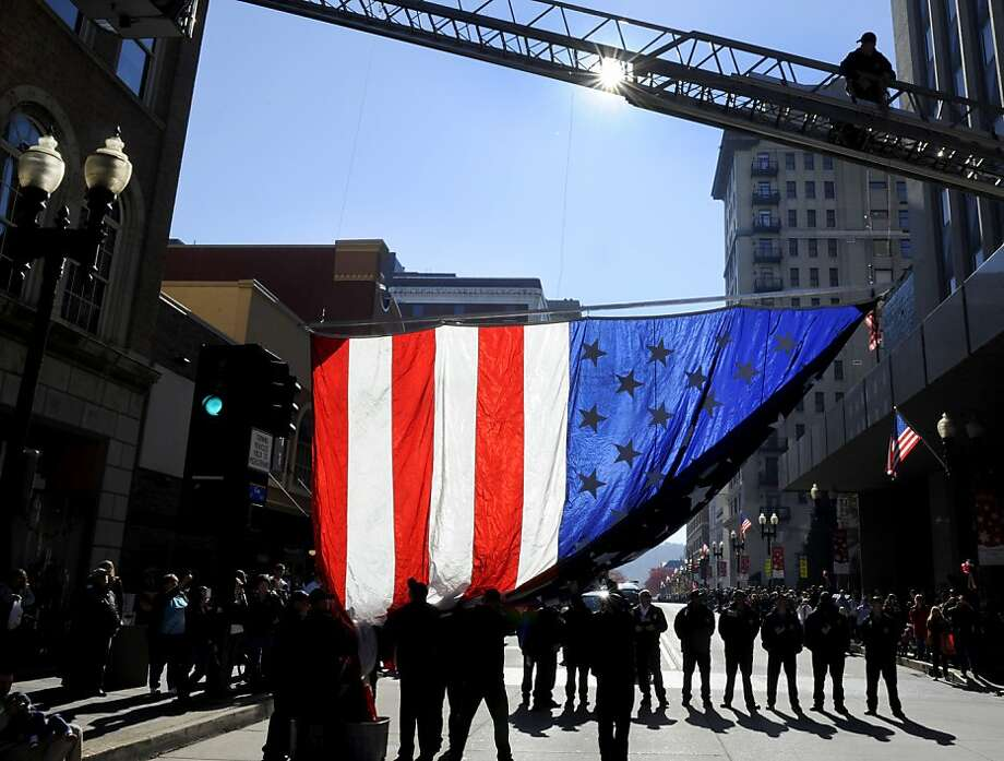 Members of the Knoxville Fire Department raise an American flag over Gay Street in Knoxville, Tenn., before the start of the city's 87th Veterans Day Parade on Friday, Nov. 9, 2012. Thousands lined up to watch the 90-minute parade.  (AP Photo/Knoxville News Sentinel, Michael Patrick) Photo: Michael Patrick, Associated Press