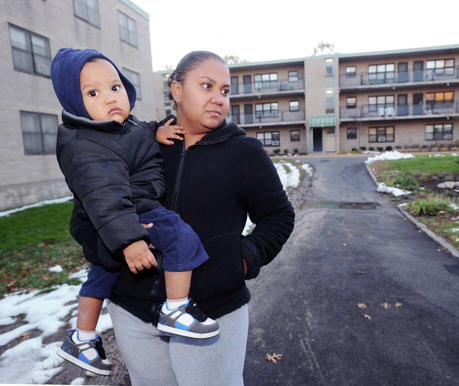 Armstrong Court resident Yenny Lujan holds her son, Erickson, 14 months old, while speaking to a reporter about the hardships her family endured because of Hurricane Sandy, at the public housing complex in Greenwich, Friday afternoon, November 9, 2012. Photo: Bob Luckey / Greenwich Time