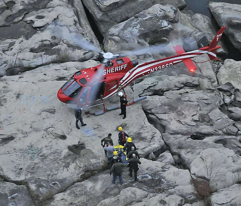 Members of the Niagara Falls Fire Department, New York State Parks Police, and the Erie County Sheriff Department carry a woman that was found in the Niagara River clinging to rocks to a waiting helicopter, Friday, Nov. 9, 2012, down in the Niagara Gorge at Whirlpool State Park in Niagara Falls, N.Y. The woman apparently slipped while walking in the Niagara Gorge. (AP Photo/The Niagara Gazette, James Neiss) Photo: James Neiss, Associated Press