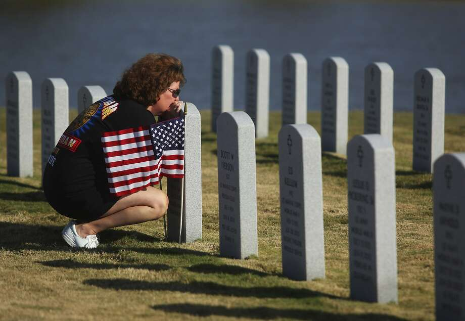 Debbie Gregory places flags recently at the National Cemetery grave of her husband, former Marine Cpl. Paul Gregory, who died from cancer caused by exposure to Agent Orange. Photo: Mona Reeder, Associated Press