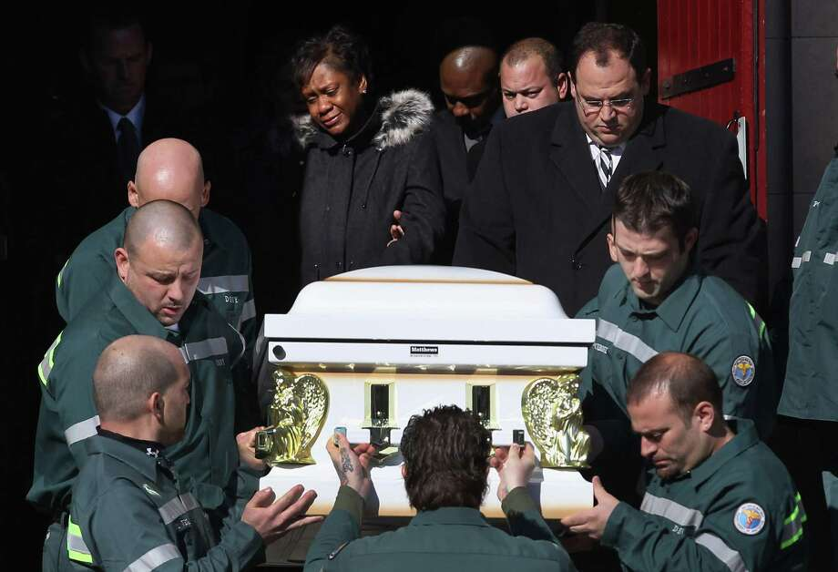 Glenda Moore (C) watches as New York sanitation department workers carry a casket containing the bodies of her two sons after their funeral at the St. Rose of Lima Catholic church on November 9, 2012 in the Brooklyn borough of New York City. Brandon Moore, 2, and his brother Connor Moore, 4, were swept away from the arms of their mother Glenda as she fled with them from Superstorm Sandy floodwaters in New York's Staten Island borough to seek safety with family in Brooklyn the night of the storm. She is married to New York sanitation worker Damian Moore, and dozens of workers and officials from the sanitation department attended the funeral ceremony. Photo: John Moore, Getty Images / 2012 Getty Images