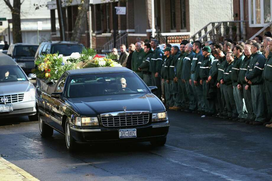 New York sanitation department workers watch as a hearse arrives with a casket carrying the bodies of two brothers killed during Superstorm Sandy for a funeral at the St. Rose of Lima Catholic church on November 9, 2012 in the Brooklyn borough of New York City. Brandon Moore, 2, and Connor Moore, 4, were swept away from the arms of their mother Glenda Moore as she fled Superstorm Sandy floodwaters in New York's Staten Island borough to seek safety with family in Brooklyn. Photo: John Moore, Getty Images / 2012 Getty Images
