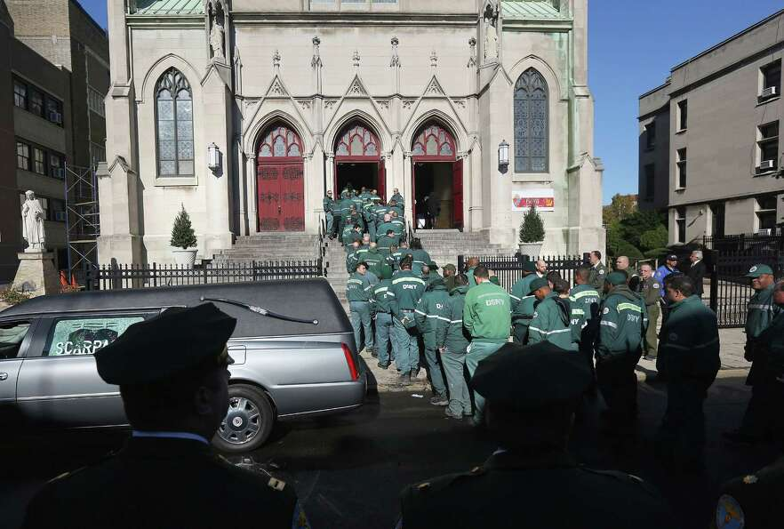 New York sanitation department workers enter the St. Rose of Lima Catholic church for a funeral for