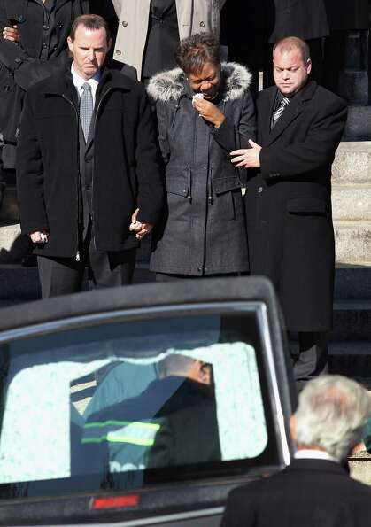 Damian Moore (L), and his wife Glenda Moore (C) are escorted as the casket carrying their two sons i