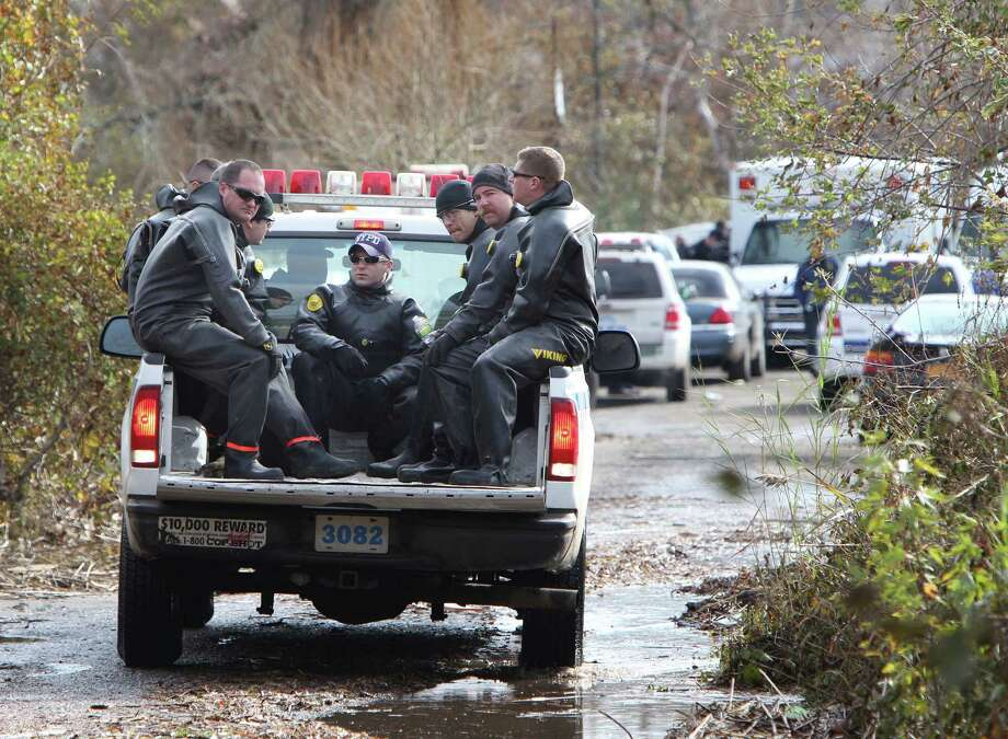 Police officers wearing wet suits leave a site where the body of a 2-year-old child killed during Superstorm Sandy was discovered in Staten Island, New York, Thursday, Nov. 1, 2012.  Brandon Moore, 2, and Connor Moore, 4, were swiped into swirling waters as their mother tried to escape her SUV on Monday amid rushing waters that caused the vehicle to stall during Superstorm Sandy. Photo: Seth Wenig, Associated Press / AP