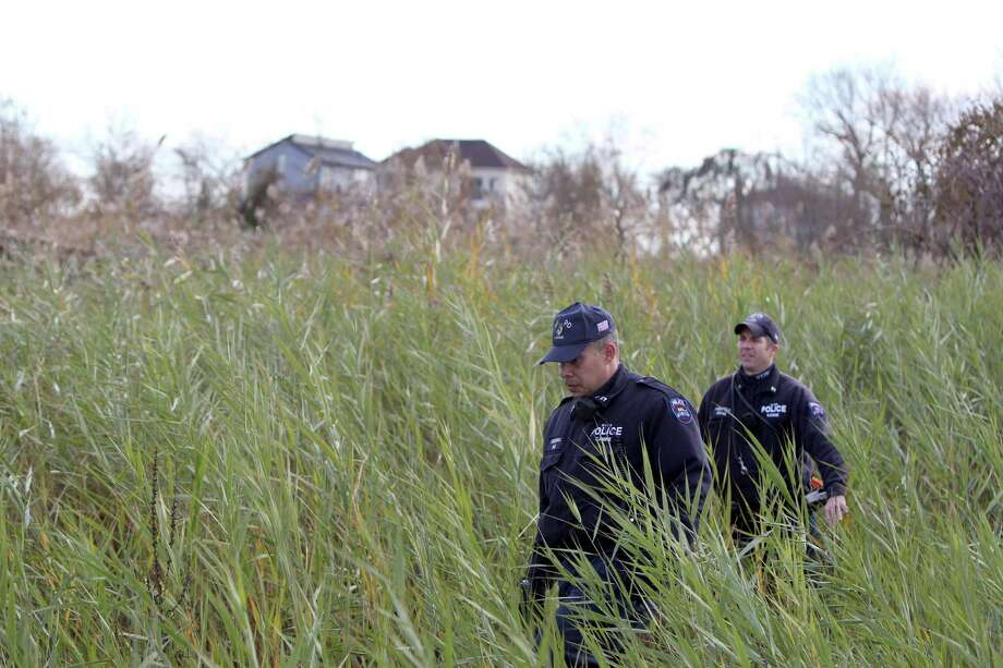 Police officers wearing wet suits leave a site where the body of a 2-year-old child killed during Superstorm Sandy was discovered in Staten Island, New York, Thursday, Nov. 1, 2012. Photo: Seth Wenig, Associated Press / AP