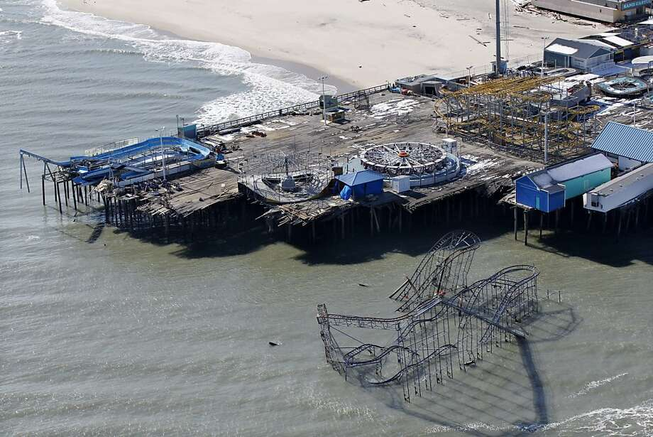 In this aerial photograph, the broken amusement pier dangles over the Atlantic Ocean in Seaside Heights, N.J., Friday, Nov. 9, 2012, after the region  was pounded by Superstorm Sandy last week. (AP Photo/Mel Evans) Photo: Mel Evans, Associated Press