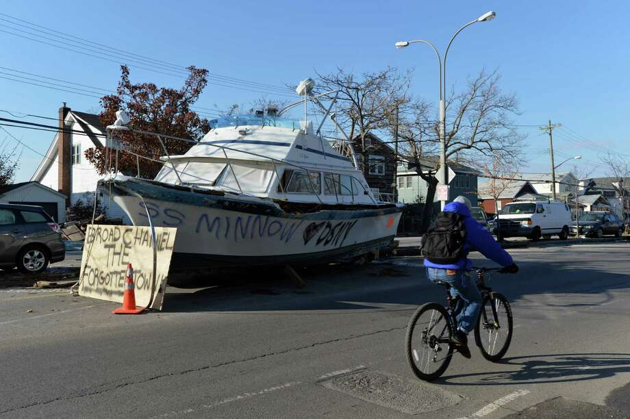 "A boat and other debris sit on Cross Bay Boulevard in the Broad Channel section of Queens on November 9, 2012 in New York as the region continues to recover from the effects of Hurricane Sandy. A sign by the boat says, ""Broad Channel The Forgotten Town"". Photo: STAN HONDA, AFP/Getty Images / AFP"