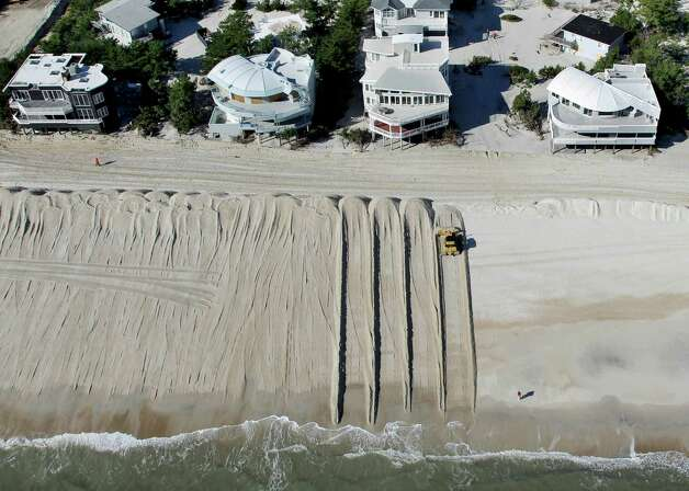 In this aerial photograph, heavy equipment pushes sand to restore a barrier dune along the Atlantic Ocean in Harvey Cedars on Long Beach Island, N.J., Friday, Nov. 9, 2012, after the region was pounded by Superstorm Sandy the previous week. Photo: Mel Evans, Associated Press / AP