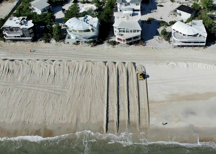 In this aerial photograph, heavy equipment pushes sand to restore a barrier dune along the Atlantic