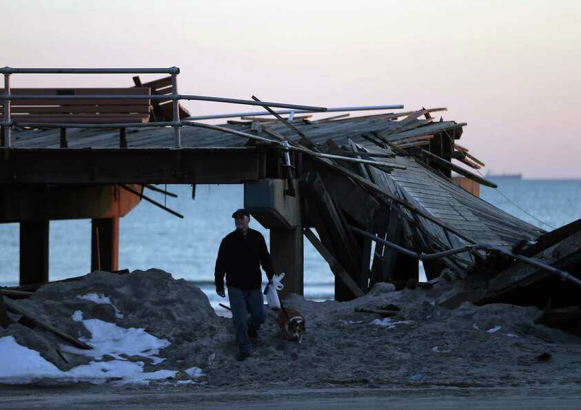 A man walks past a destroyed section of the boardwalk at the base of Lincoln Boulevard as Long Islan