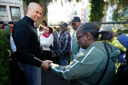 Grace Harris, right, gives her hand to Newark, N.J. Mayor Cory Booker to show just how cold her body is as she waits in line to get clothing donations at Clinton Hill Community Resource Center, Friday, Nov. 9, 2012, in Newark, N.J. Harris was among people who lined up to get warm clothing as temperatures dropped following Superstorm Sandy. Photo: Julio Cortez, Associated Press / AP