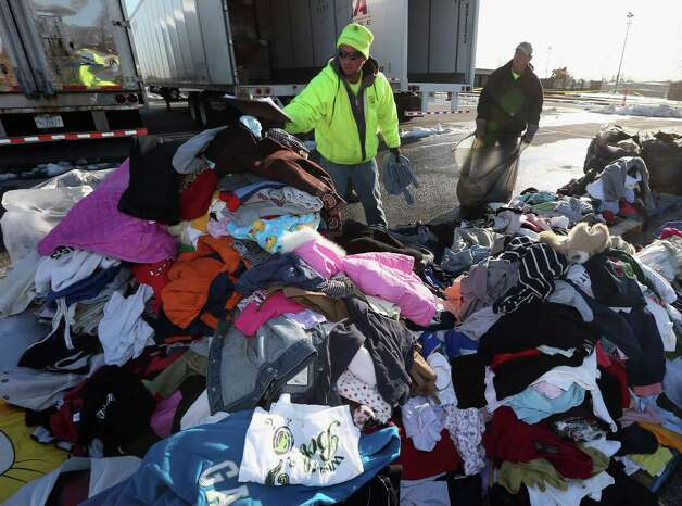 James Vouloukos and William Ferris sort through donated clothes at a site maintained by the Town of Hempstead in cooperation with FEMA at Oceanside Park during in the aftermath of Superstorm Sandy on November 9, 2012 in Oceanside, New York. New York Gov. Andrew M. Cuomo has said that the economic loss and damage to homes and businesses caused by Sandy could total $33 billion in New York, according to published reports. Photo: Bruce Bennett, Getty Images / 2012 Getty Images