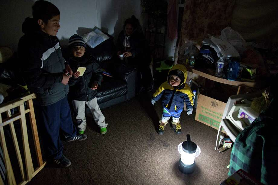 Living through another night of possibly freezing temperatures, Michael Pineda, fifteen months old, stands bundled up near a battery operated lantern in his home without power or heat in the Rockaway Park neighborhood in the Queens borough of New York, Thursday, Nov. 8, 2012, in the wake of Superstorm Sandy. From left is his brother Mario Pineda, 12, Walter Rivera, 5, and center in deep shadow is their mother Fatima Pineda. Photo: Craig Ruttle, Associated Press / FR61802 AP