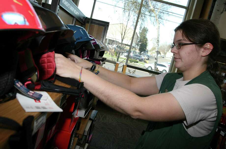 REI employee Jane Gette arranges ski helmets at the Norwalk, Conn. store on Friday, Nov. 9, 2012. Photo: David Ames / Greenwich Time Freelance