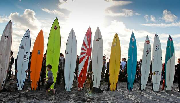Surfers line up with their surfboards before paddling into the ocean. The surfing event could be held anytime through March 31. Photo: John Storey, Special To The Chronicle