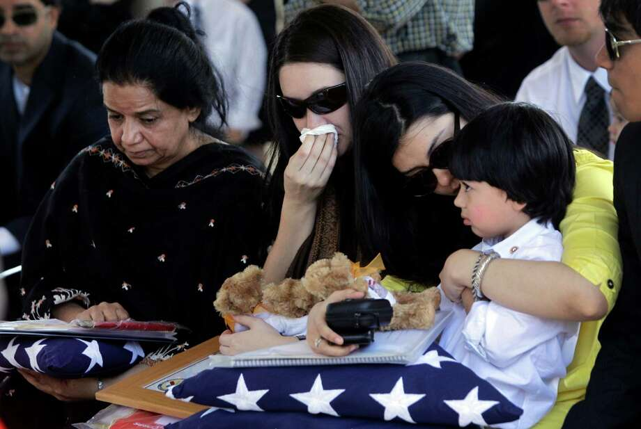 During service for U.S. Army Staff Sgt. Kashif M. Memon, his mother, Shazia Memon, left, his wife,Christina Louise Tompkins, and his sister, Anhar Memon, holding his son, Humayun Memon, 4, hold flags presented to them during service at the National Cemetery Friday, Nov. 9, 2012, in Houston.  Memon, 31, assigned to the 96th Civil Affairs Battalion (Airborne) died on Oct. 25 in Afghanistan. Photo: Melissa Phillip, Houston Chronicle / © 2012 Houston Chronicle