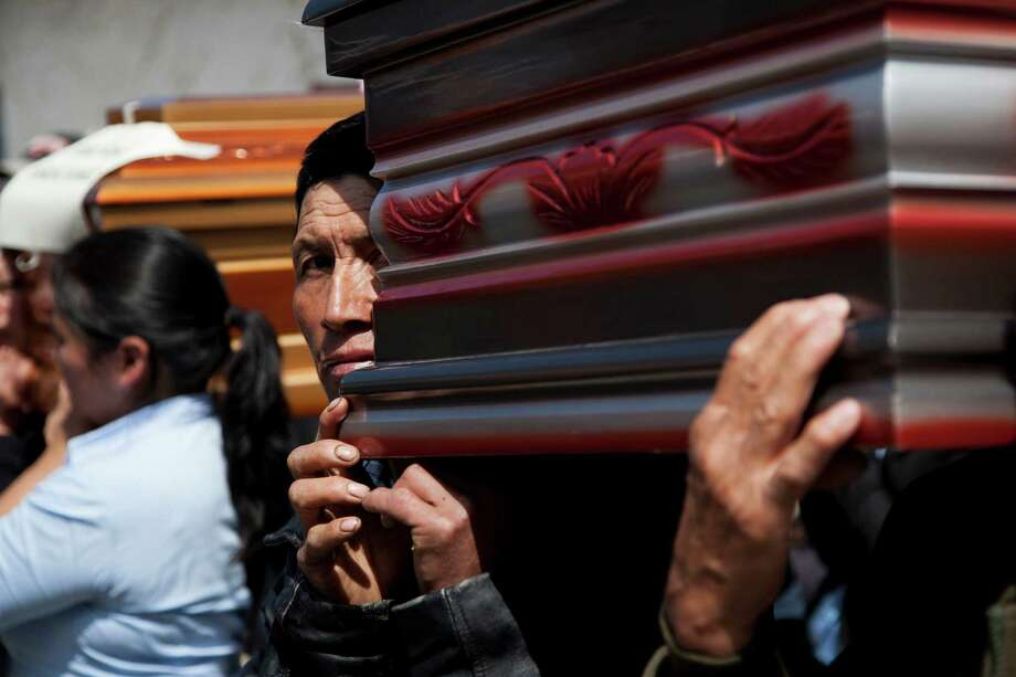 A man helps carry a coffin during the funeral procession for 10 members of the Vasquez family who died when an earthquake struck San Cristobal Cucho, Guatemala, Friday, Nov. 9, 2012. The family died when a magnitude 7.4 earthquake struck on Wednesday, collapsing their home and burying them, including a 4-year-old child, in the rubble. The powerful quake killed at least 52 people and left dozens more missing. Photo: Moises Castillo, Associated Press / AP