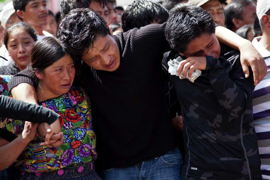 Ivan Vasquez, 19, the only survivor of his family after an earthquake, center, is helped during the funeral procession of his family in San Cristobal Cucho, Guatemala, Friday, Nov. 9, 2012. Ivan's parents, six siblings and two cousins died when a magnitude 7.4 earthquake struck on Wednesday, collapsing their home and burying them, including a 4-year-old child, in the rubble. The powerful quake killed at least 52 people and left dozens more missing. Photo: Moises Castillo, Associated Press / AP
